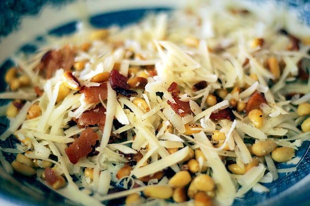 shredded cheese, bacon, and pine nuts in a blue willow bowl