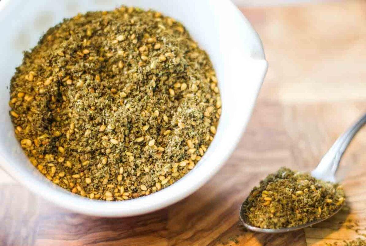 zaatar spice in a white bowl on a cutting board
