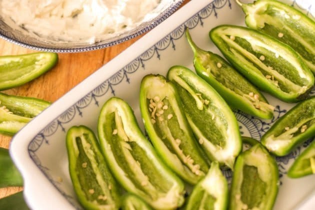jalapeno peppers cut in half on a white blue rimmed plate