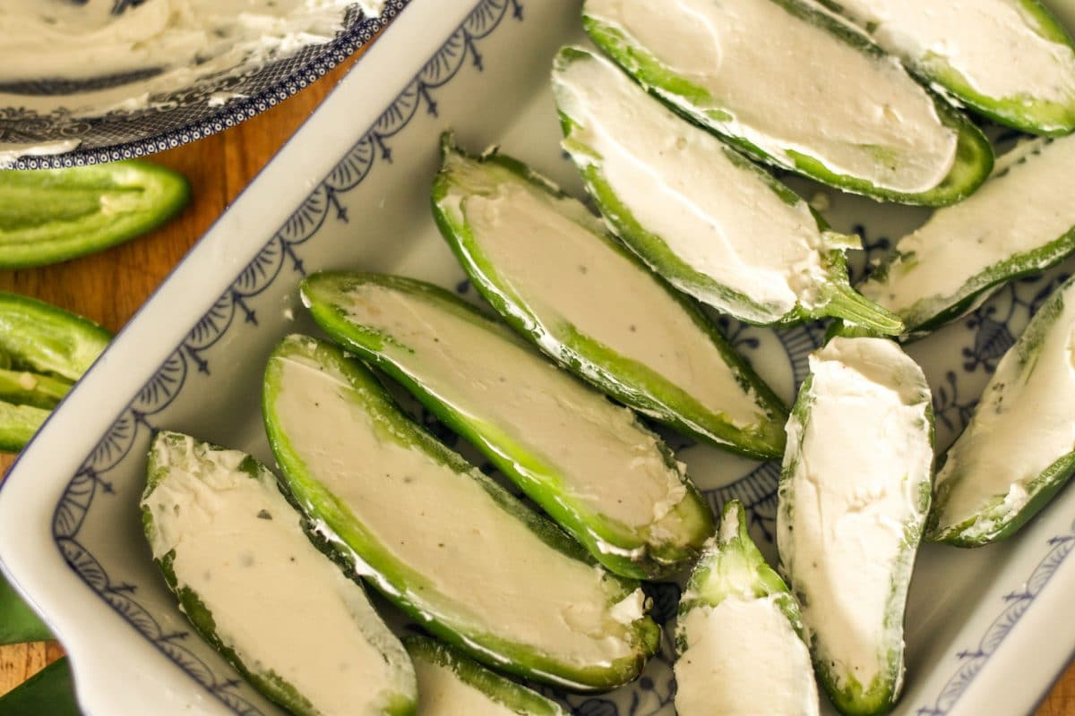 cream cheese-stuffed jalapeno halves on a white dish with blue detail