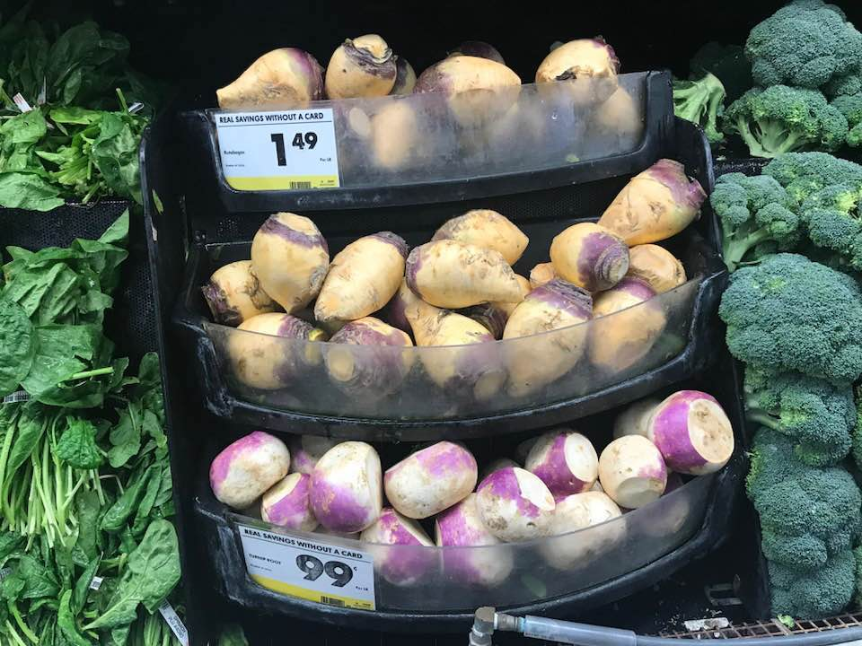 turnips and rutabagas in a grocery display