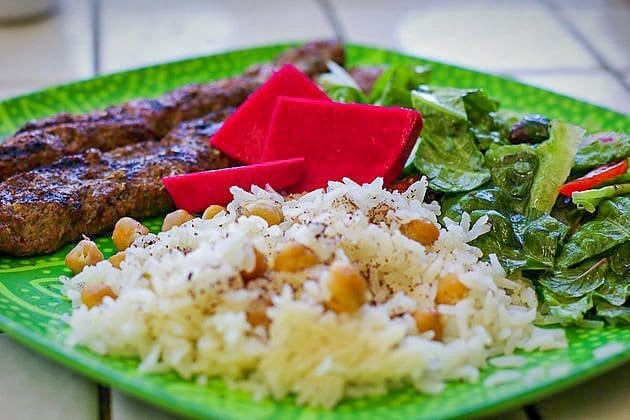 chickpea rice on a plate with kabobs