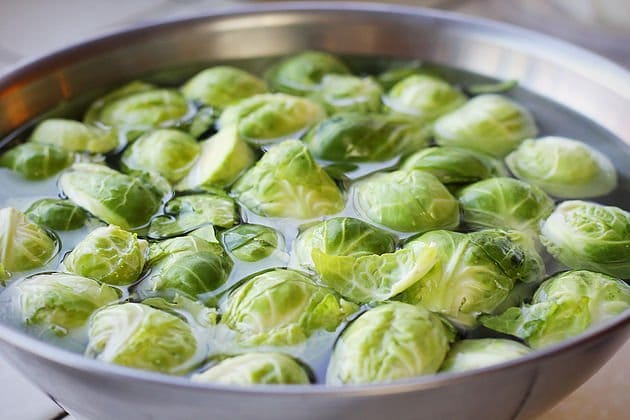 Brussel sprouts soaking in water in a bowl