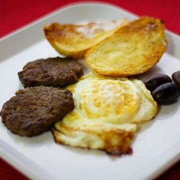 basturma and eggs and toast on a white plate with a red background
