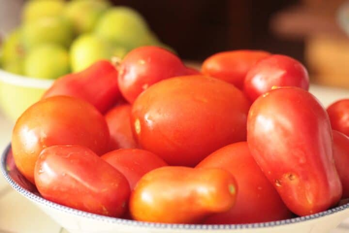 red tomatoes in a bowl with green tomatoes in the background