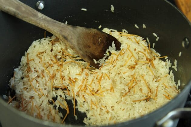 rice being stirred with a wooden spoon