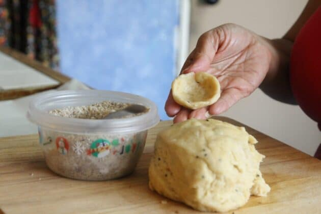 kileche dough on a cutting board in a lady's hand, with some walnut filling on the side