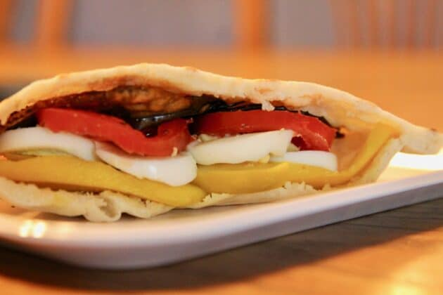 Sabich sandwich with pickled mango, tomatoes, boiled eggs and eggplant