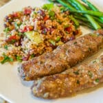 kofta kabob, salad, and asparagus on a white plate