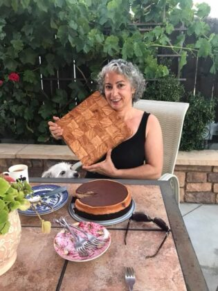 a lady holding up a cutting board while sitting outside