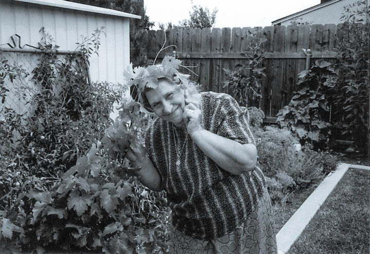 an old lady in the garden with grape leaf vine around her head