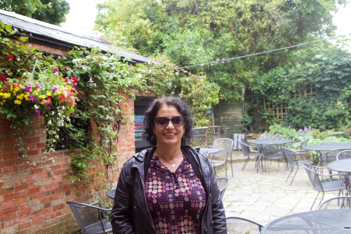 a lady standing in a beautiful garden for a restaurant