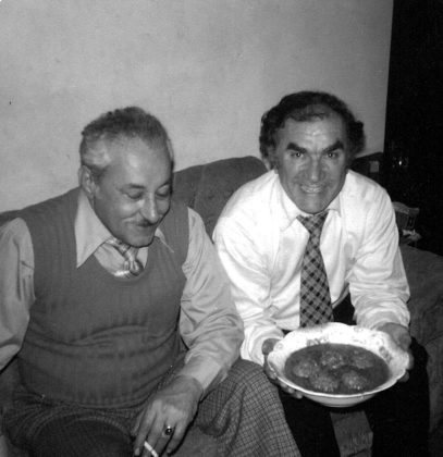 two men sitting on a couch, one is holding a bowl of meatball soup/chipteh