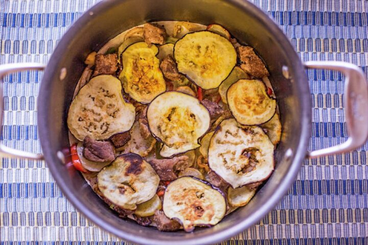 layers of meat, peppers, and sliced eggplant in a pot for Maglooba