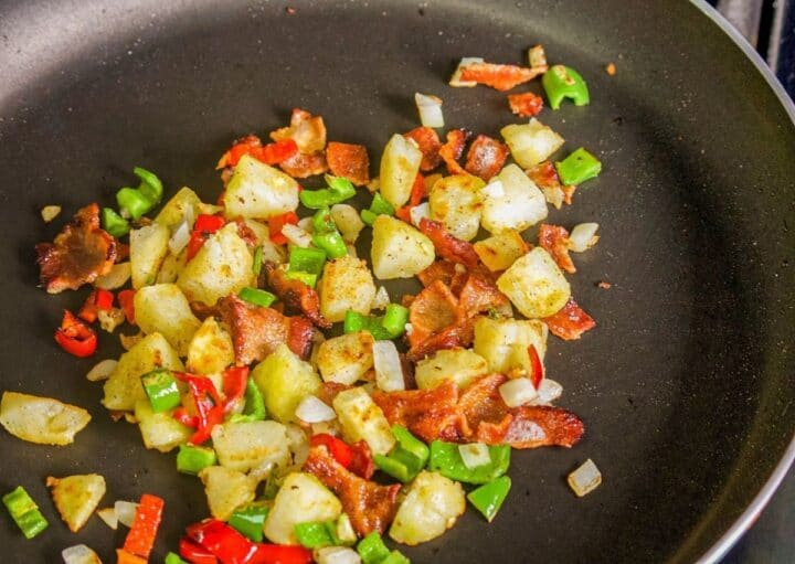 diced potatoes onions and peppers in a pan