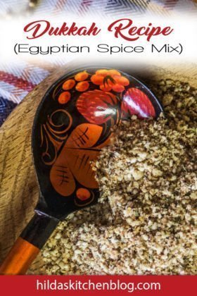 dukkah spice blend being spooned with a black and orange spoon