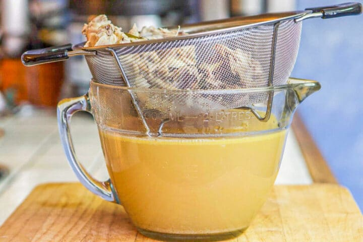chicken broth in a large measuring cup with strainer over it