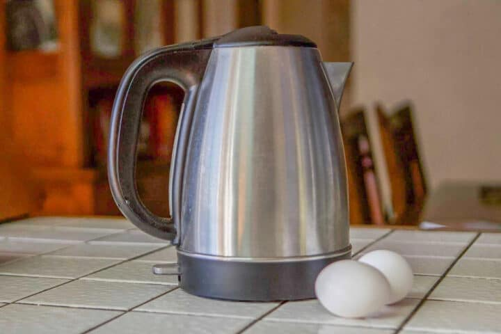 tea kettle and 2 eggs next to it