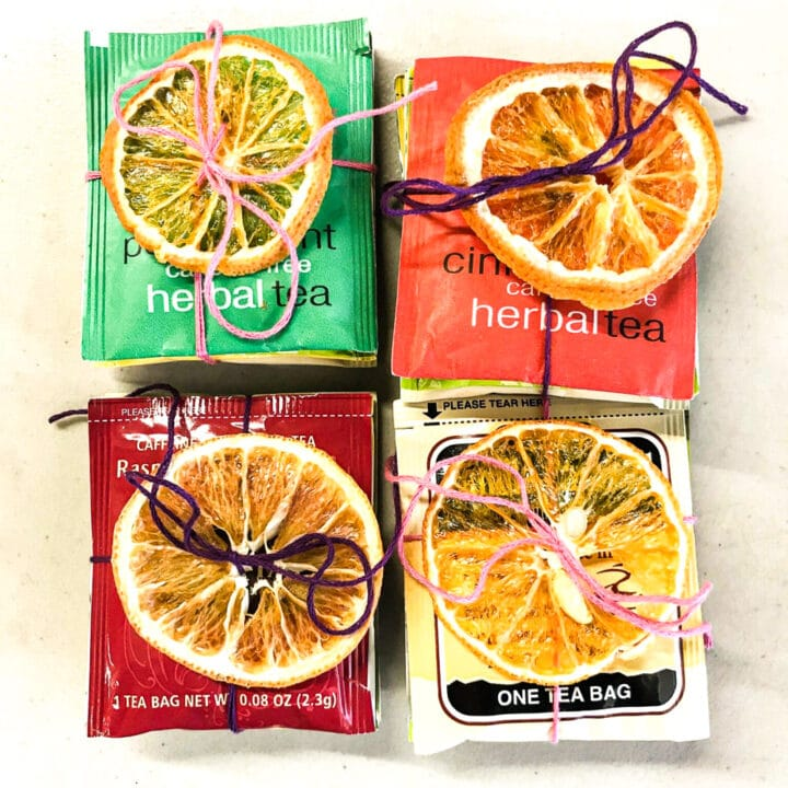tea bags with orange slices tied to them