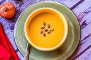 roasted pumpkin soup in a bowl with a red napkin and salt shaker