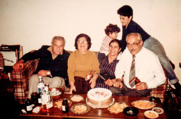 an Assyrian family in the 1980's celebrating an anniversary with cake and other snacks on a table, while they crowd on a couch