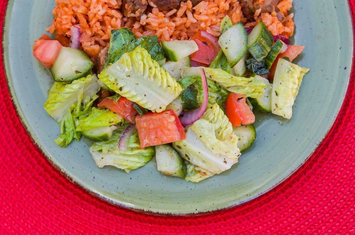 salad and red rice on a green plate and a red place mat