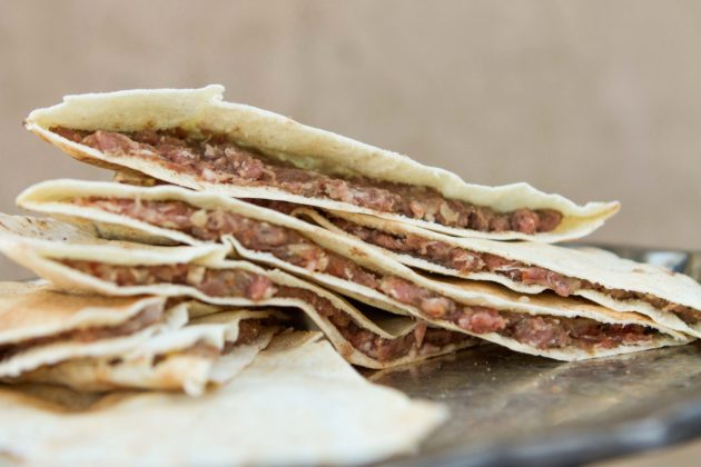 stacked half pitas full of raw meat mix