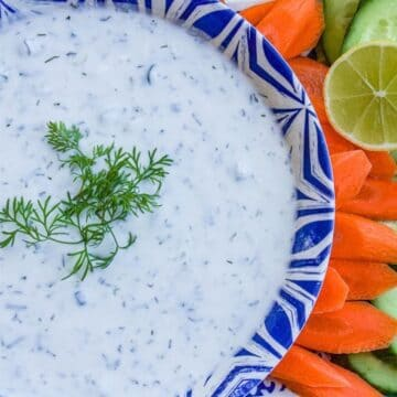 yogurt dip in a bowl, with carrots and a lime wedge
