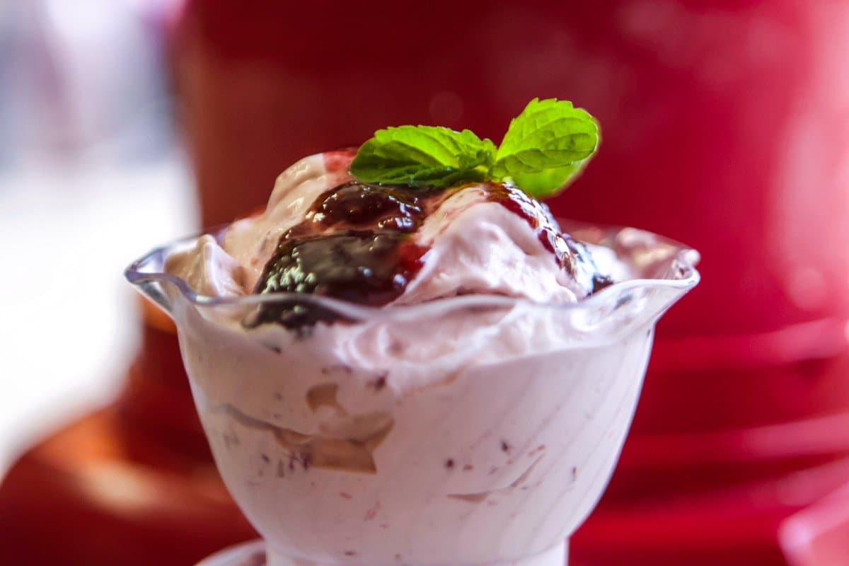 cup of ice cream with raspberry preserves, topped with two mint leaves, with a red ice cream maker in the background