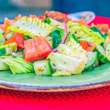 salad on a green plate over a red mat