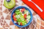 salad in a blue bowl on a mosaic table
