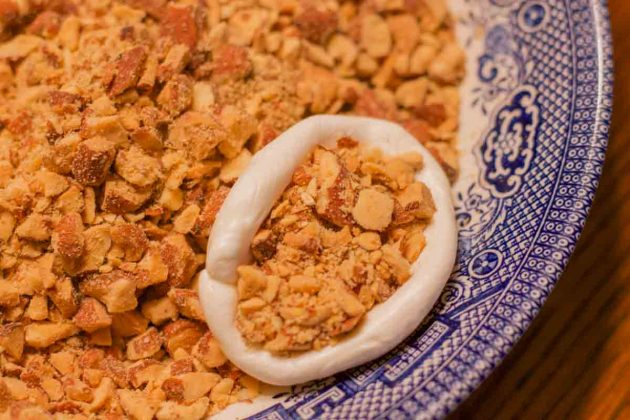 nougat stuffed with nuts on a blue plate with chopped nuts