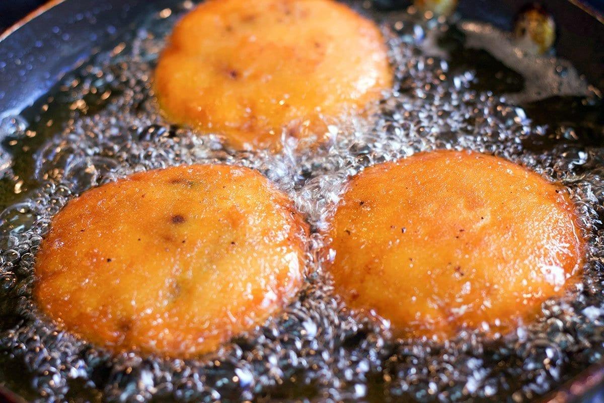 3 potato patties being fried in oil