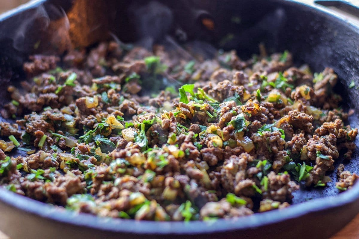 ground beef in a pan with onions, and parsley