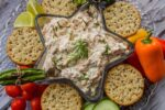 smoked salmon dip in a star shaped dish with crackers and vegetables