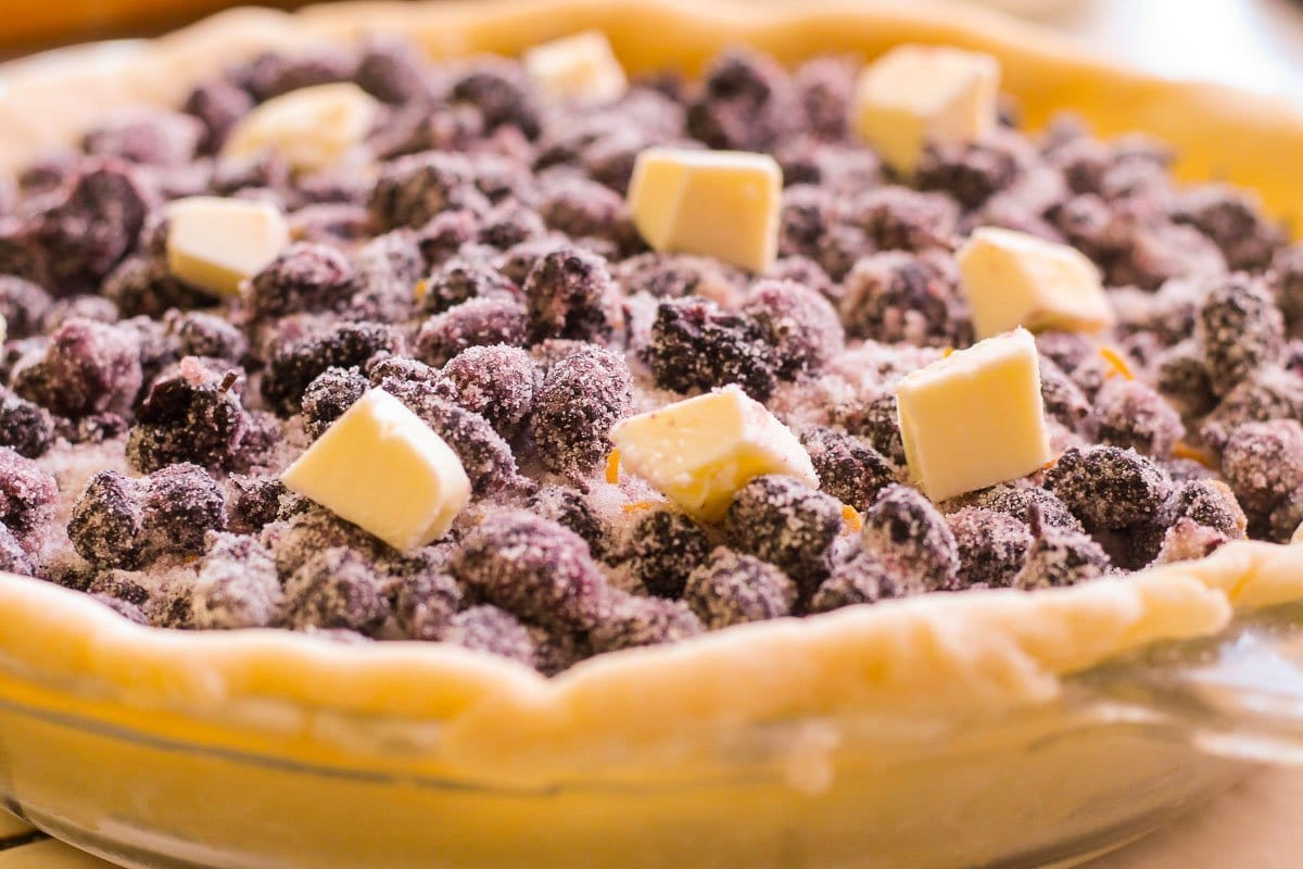 unbaked mulberry pie dotted with butter