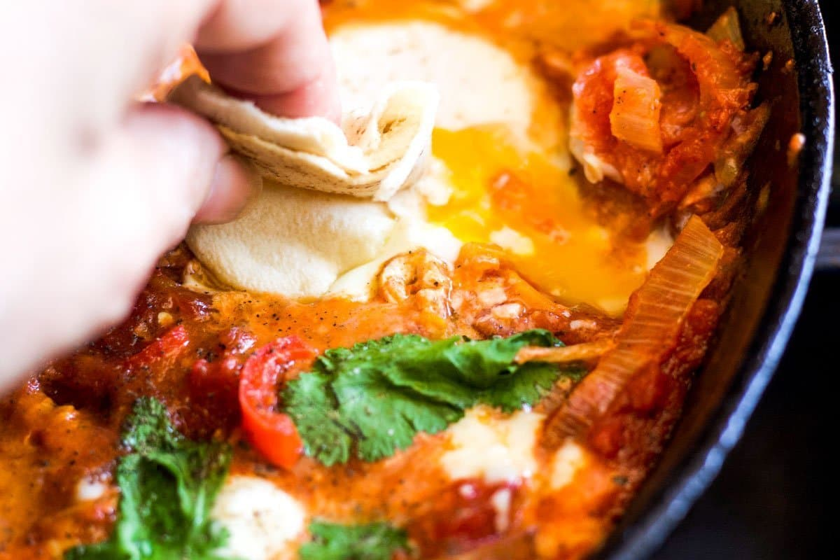 shakshuka with pita bread being dipped into it