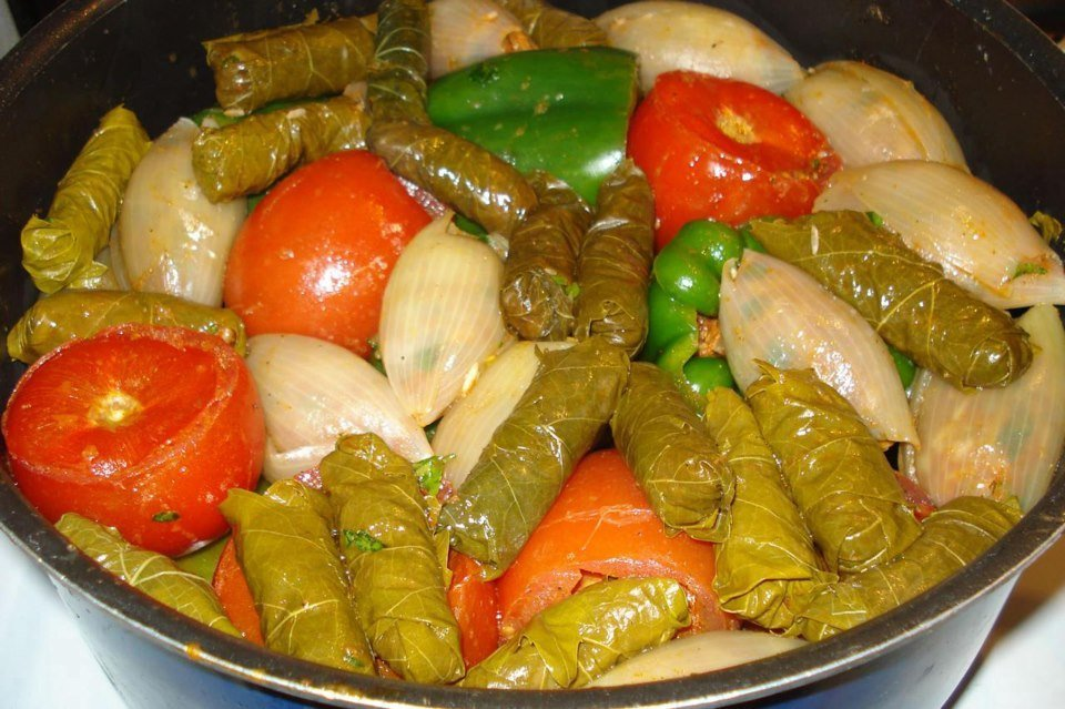 dolma made with grape leaves, tomatoes, and green peppers