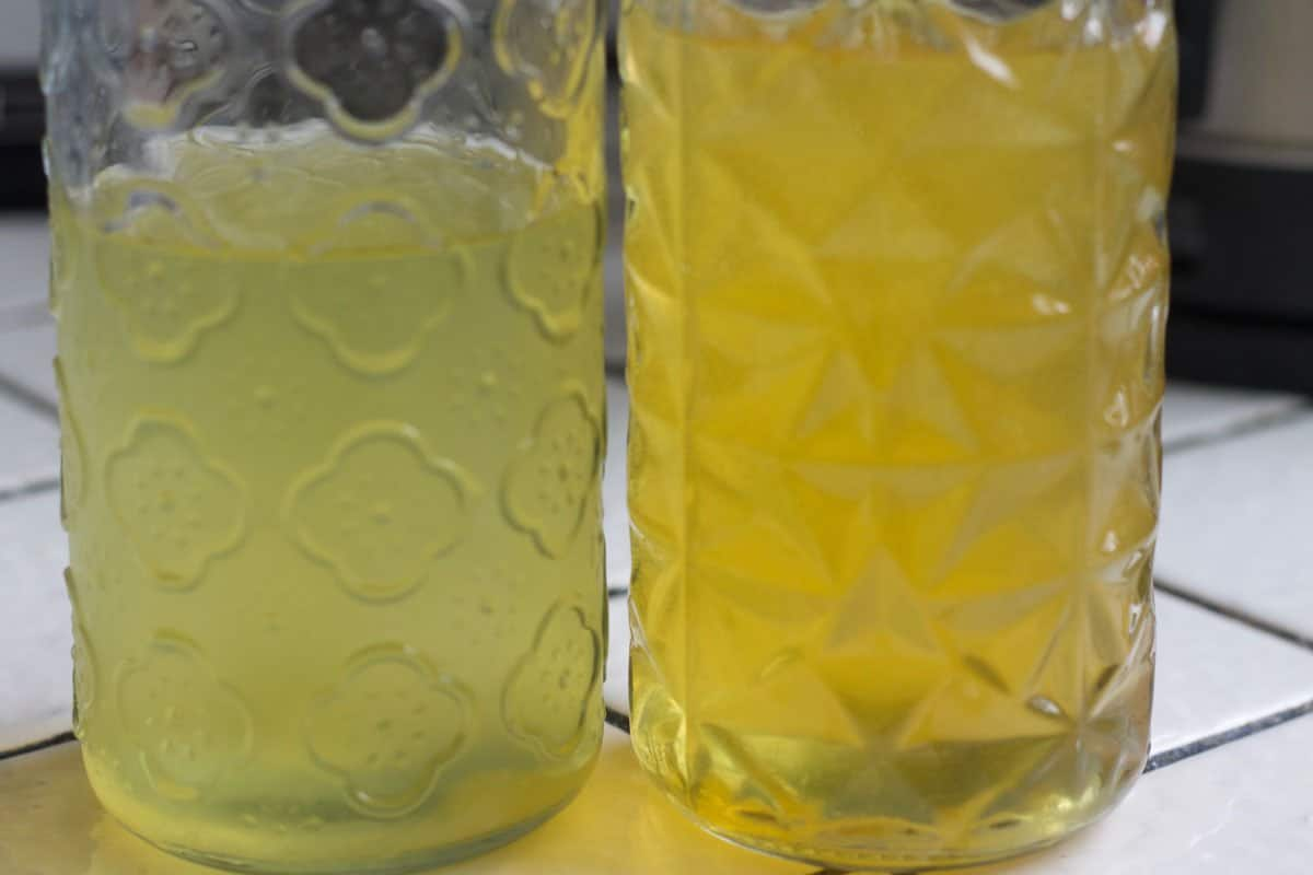 two bottles with yellow liquid