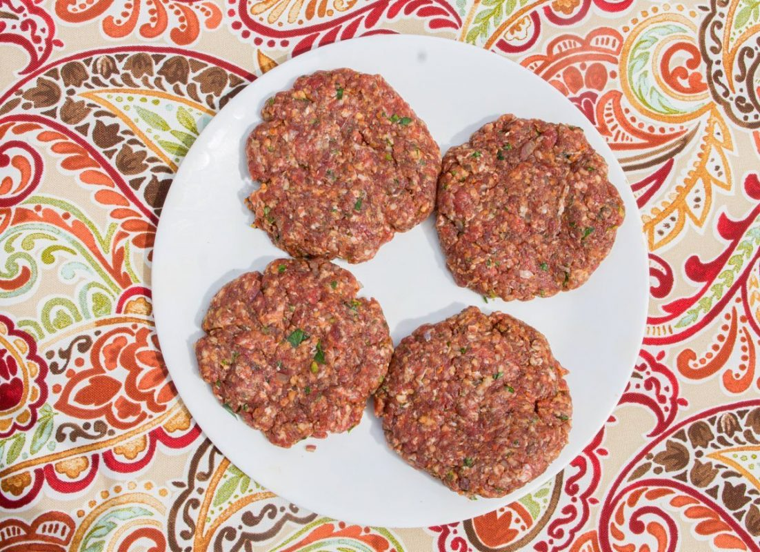 four raw meat patties on a white plate