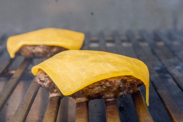 two elk cheeseburgers on a grill