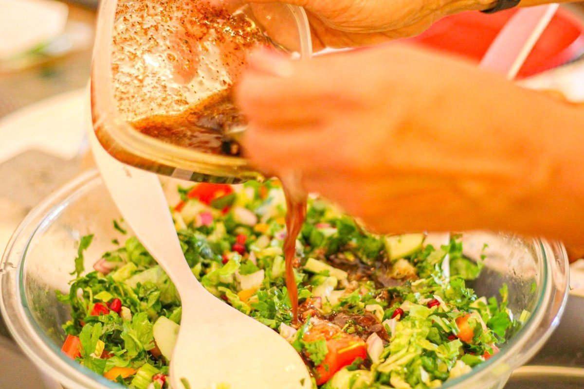 fattoush salad with dressing being poured over it