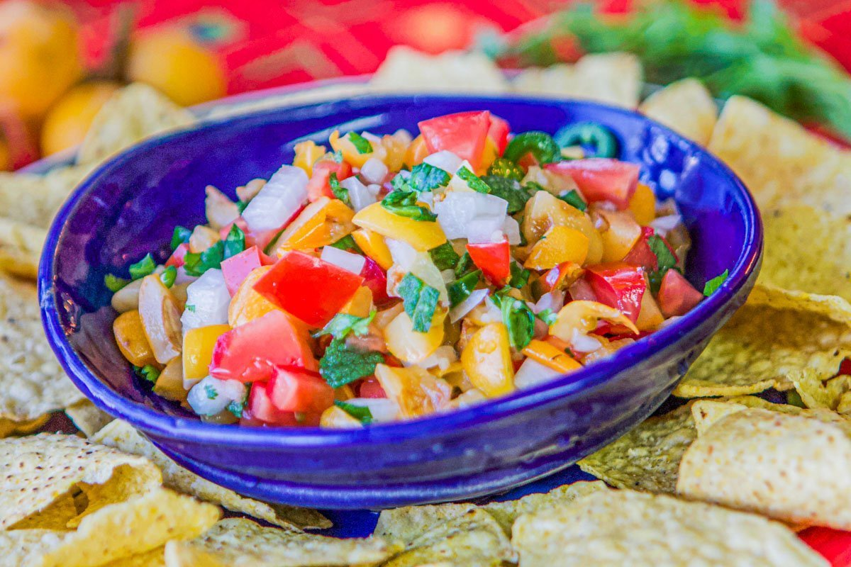 loquat fruit salsa in a blue bowl with chips