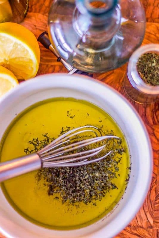 salad dressing with whisk in white bowl
