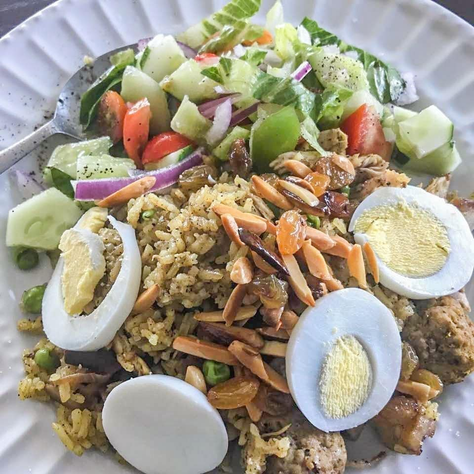 chicken biryani recipe with a green salad on a white plate