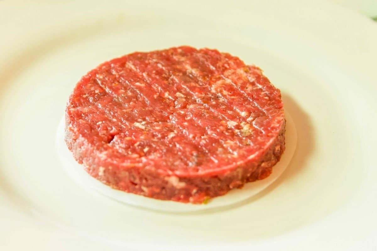 raw bison burger on a white plate