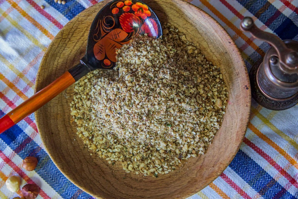 dukkah spice blend in a bowl over a blue and orange striped dish cloth