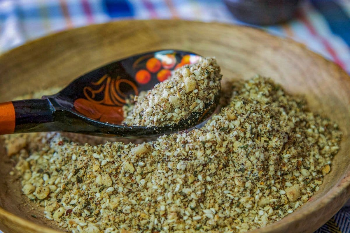 dukkah spice in a wooden bowl with a black and orange spoon