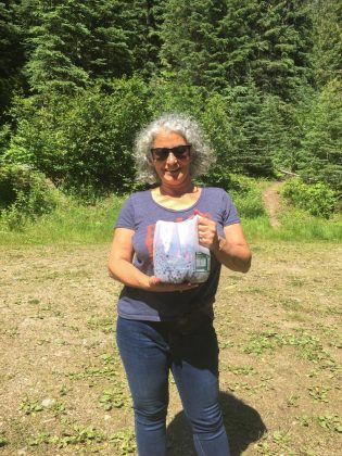 lady holding a jug full of huckleberries for pie