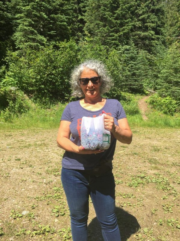 lady holding a jug full of huckleberries
